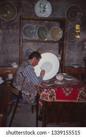 AVANOS,  TURKEY - MAY 29, 1999 - Artist paintig a porcelain plate before kiln firing, Avanos, Turkey