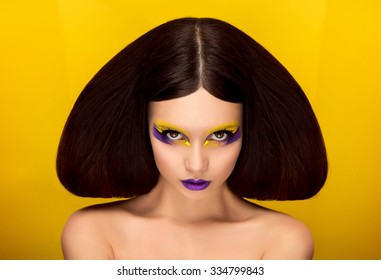 The avantaged portrait girl with an unusual make up looking at the camera, Portrait on a yellow background, custom volume hairstyle metal ornament in the form of fragments,fashionable toning