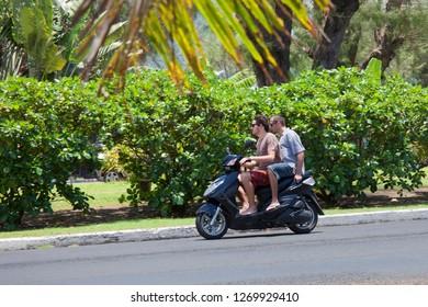 AVARUA, COOK ISLANDS - FEBRUARY 5, 2009: Two Men Riding Motorbike - Rarotonga, Cook Islands, Polynesia, Oceania