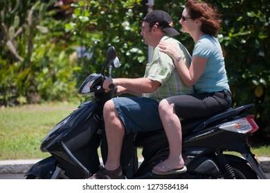 AVARUA, COOK ISLANDS - FEBRUARY 5, 2009: Mature Couple Riding Motor Scooter in Avarua, Cook Islands.