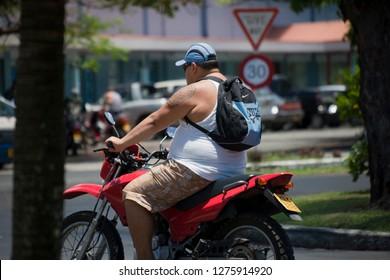 AVARUA, COOK ISLANDS - FEBRUARY 5, 2009: Man Riding Motorbike in Avarua, Cook Islands.