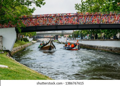Aveiro, Portugal - April 29, 2019: Traditional boat, Moliceiro, transporting tourists passing under bridge covered in confetti on canal at Aveiro, Portugal