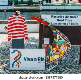 Aveiro, Portugal - April 29, 2019: Juxtaposition of facade of traditional moliceiro boat and gondolier with cut out next to a charming canal