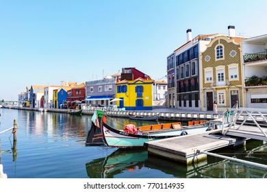 """Aveiro / Portugal August 13, 2017. Channel with the boats called """"moliceiros"""" seen from the square called """"Do peixe"""" (of the fish). On one side, typical village house painted blue and yellow"""