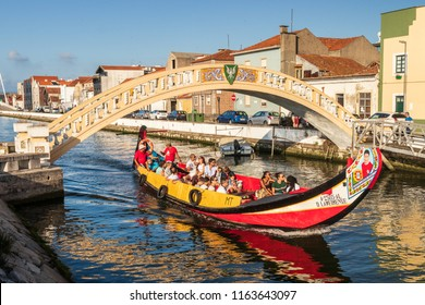 Aveiro, Portugal. July 28, 2018. Traditional boat, Moliceiro, transporting tourists passing under Carcavelos bridge at the São Roque canal in Aveiro, Portugal.