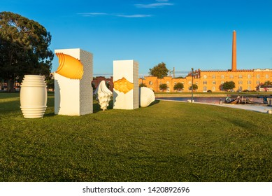 Aveiro, Portugal - June 08, 2019: Monument to the Ovos Moles de Aveiro (soft eggs from Aveiro) with the Congress Center of Aveiro in the background, on a late spring afternoon with blue sky.