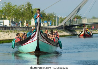 AVEIRO, PORTUGAL - May 15, 2016: Tourists enjoy a guided boat tour in a traditional Moliceiro boat in Aveiro, Portugal.