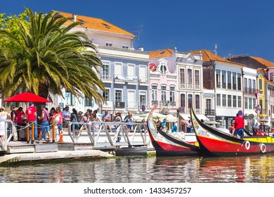 Aveiro, Portugal – May 3, 2019:  Moliceiro traditional colorful boats docked along the central charming  canal with cozy houses in Aveiro. Famous town Aveiro is known as the Venice of Portugal.