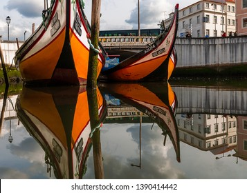 Aveiro, Portugal - May 6 2019: Two yellow moliceiro tourist boats on the canal in Aveiro reflected in the water. Aveiro is known as the Venice of Portugal because of its canals