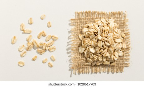 Avena Sativa is scientific name of Oat cereal grain. Also known as Aveia or Avena. Close up of grains spreaded over white table.