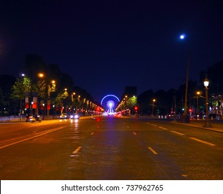 Avenue Champs-Elysees with illumination and ferris wheel at horizon in Paris, France. Champs-Elysees is one of the most known and famous streets in the world