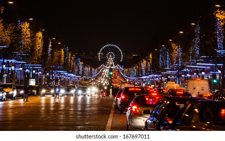 Photo of Avenue des Champs-Elysees in Paris decorated with Christmas illumination and the ferris wheel at horizon.
