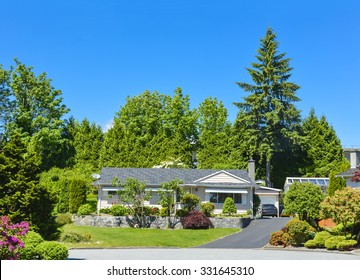 Average family house in beautiful calm place. Residential house with landscape on elevated ground terrace in front and blue sky background. Family house with asphalt driveway and  detached garage.