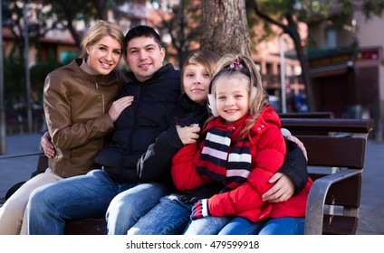 Average family with two kids sitting on bench outdoors