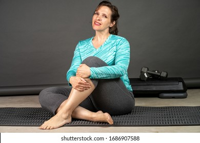 Average looking woman in her late 40s relaxing on a mat after yoga. Healthy indoor social distancing exercise concept.