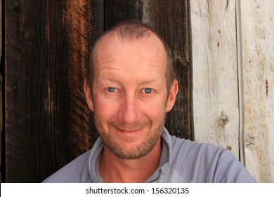 An average middle aged man with a wooden background.