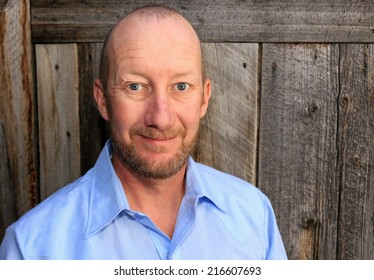 Average middle aged man with a wooden background.