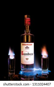 Avetrana, Italy - 09 February, 2019 A bottle of sambuca on fire, two glasses with burning sambuca, coffee grains and anise star on a black background