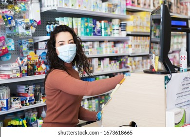 Avetrana, Italy, - Marth, 13, 2020. Beautiful young cashier with medical mask and gloves working at the supermarket. Respecting health standards during Coronavirus, quarantine covid-19