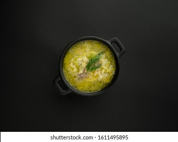 Avgolemono, traditional greek chicken soup with egg lemon sauce and dill in black pot on black background. Overhead shot.