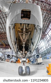 Aviation hangar with airplane, close-up front landing gear of the airplane landing gear on maintenance repair