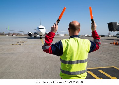 Aviation marshaller meets an airplane at the airport. Airport worker. Modern airport overview. Man at work.