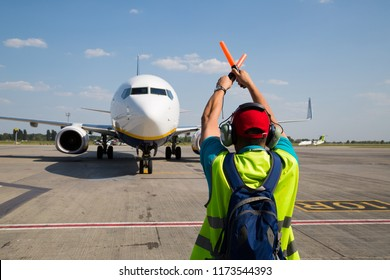 Aviation marshaller meets airplane at the airport. Airport worker. Modern airport.