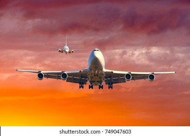 Aviation traffic. The planes take off and land on the background of a bright orange sunset sky.