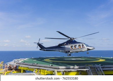Aviation transportation. View of commercial helicopter depart after taking offshoreworkers on oil and gas platform with background of South China sea.