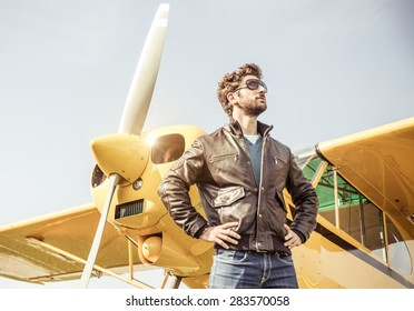 aviator posing before flight with his aircraft. concept about airplanes,pilots and people