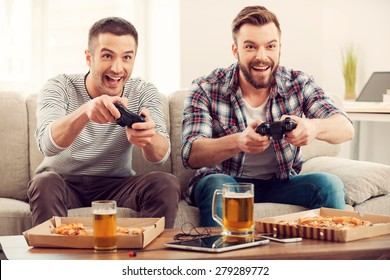 The avid gamers. Two young happy men playing video games while sitting on sofa
