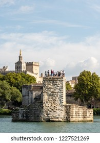 The Avignon bridge and the Papal palace in the city of Avignon, south of France. The bridge and the palace are both built in the medieval time. The river in the foreground is the Rhone.