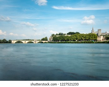 The Avignon bridge and the Papal palace are two touristic attraction built in the medieval time, in Avignon, southern France. The Rhone river cross the city. Filmed during the summer.