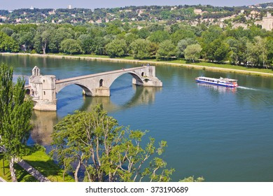 Avignon, France - 1 May 2011: A boat passing nearby the broken bridge landmark Pont Saint Benezet of Avignon