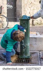 Avignon / France - 12/27/2017: Boy drinking from French fountain