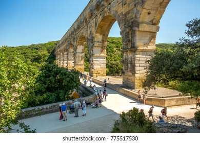 Avignon, France - 6/4/2015:  Tourists visiting Pont du Gard, a Mighty aqueduct bridge rising over 3 well-preserved arched tiers, built by 1st-century Romans.