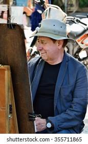 AVIGNON, FRANCE - JUL 12, 2014: Unidentified street artist painting a picture during the annual Avignon Theater Festival in Avignon.