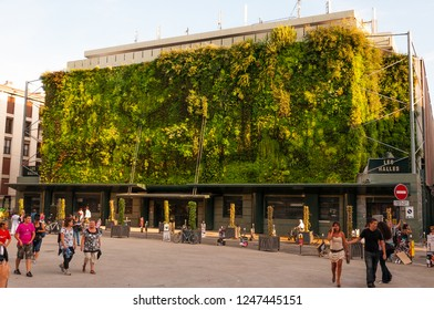 Avignon, France - July 22, 2011: Green plants living facade of Less Halles with walking around people in Avignon, France during the Art Festival Off.