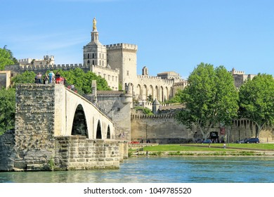 AVIGNON, FRANCE - MAY 08, 2014: tourists in the Avignon's boat taking pictures of Avignon's bridge and The Popes Palace in Avignon ( city of Popes), France