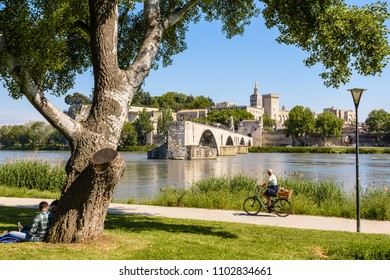 Avignon, France - May 16, 2018: People are biking or resting by a sunny day on the banks of the Rhone, opposite the Saint-Benezet bridge, also known as Avignon bridge, and the Papal palace.