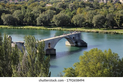 Avignon, France - October 3, 2019: Tourists walk on the famous stone bridge across the Rhone river in Avignon, France on October 3, 2019