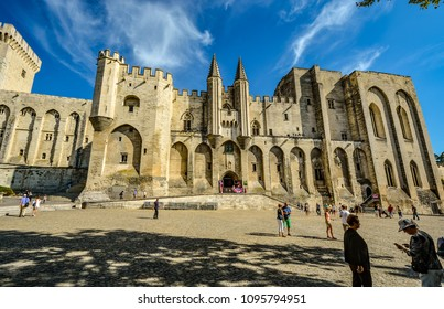 Avignon, France - September 22 2016: Tourists mingle at the square in front of the Palais des Papes or Popes Palace, a huge medieval castle and fortress in Avignon France in the Provence region