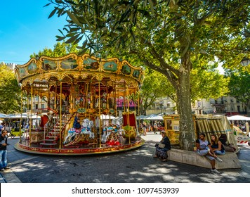 Avignon, France - September 22 2016: Tourists enjoy the colorful carousel at Place de l'Horloge in the town center of Avignon France in Provence
