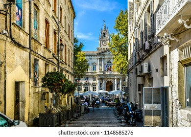 Avignon, France - September 22 2017: The main square and Avignon City Hall on a summer day with a large cafe with outdoor seating and umbrellas filled with tourists and locals in Avignon France