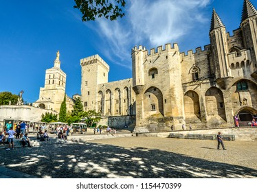 Avignon, France - September 22 2017: Tourists relax on the square in front of the medieval gothic Pope's Palace in Avignon, France.