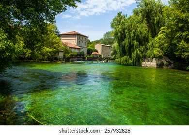 Avignon Lake & Houses.  Stucco Houses with a Red Roof in France.  An Emerald Green Lake.