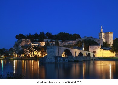 The Avignon Papal Palace (Palais des Papes) and the Avignon Bridge (Pont d'Avignon or Pont St-Bénézet) illuminated at night under the deep blue sky reflecting in the still waters of Rhone river.