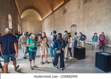 Avignon, Provence / France - September 27, 2018: Gray-haired pensioners in headphones with audio guides visit the interiors of the Papal Palace