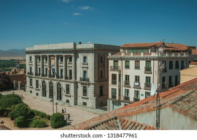 Avila, Spain - July 23, 2018. Sumptuous building facade with flags in front of square at Avila. It has the longest and imposing wall completely encircling this well-kept gothic town of Spain.