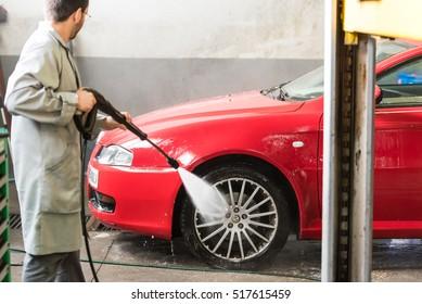 AVILA, SPAIN - NOVEMBER 9,2016: A mechanic cleans an alfa romeo car with a high pressure water hose at a car repair shop (motor garage).